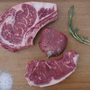 premium steaks raw on a wood surface with salt and garnish
